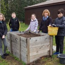 Kinder der 6. Klasse B und Frau Dr. Weber am Kartoffel-Zwiebel-Hochbeet, das nochmal mit guter Erde versorgt wurde (Foto: Dr. A. Weber)
